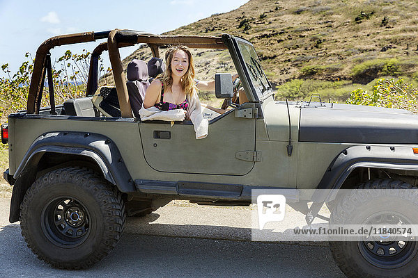 Mixed Race woman sitting in convertible car