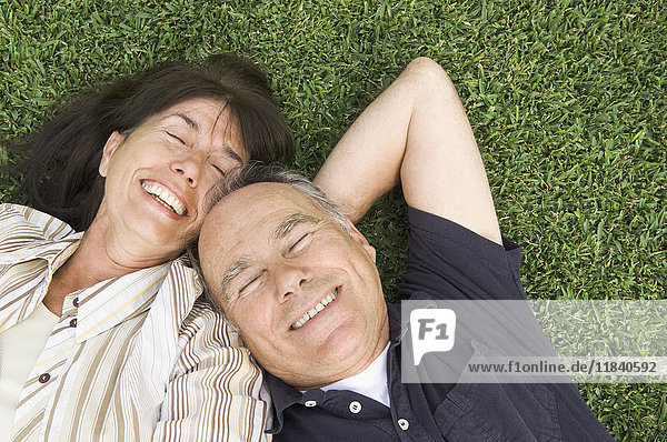 Senior couple laying in grass