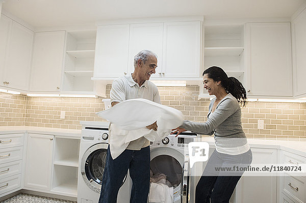 Playful couple folding towel in modern laundry room