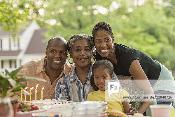 Portrait of smiling multi-generation family celebrating with cake