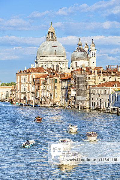 Vaporettos (water taxis) passing the grand church of Santa Maria della Salute  on the Grand Canal  Venice  UNESCO World Heritage Site  Veneto  Italy  Europe