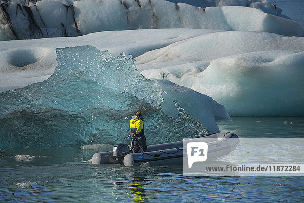 'Man riding in a zodiac among icebergs in the glacial lagoon  Jokulsarlon along the south coast of Iceland; Iceland'