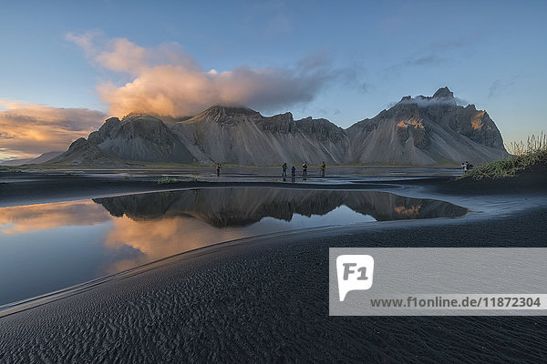 'People photographing the beautiful landscape of Stokknes or Vestrahorn at sunset along the southeast coast of Iceland; Iceland'