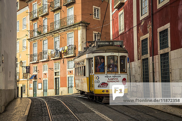 'A tram travels down the tracks beside buildings  Alfama; Lisbon  Portugal'
