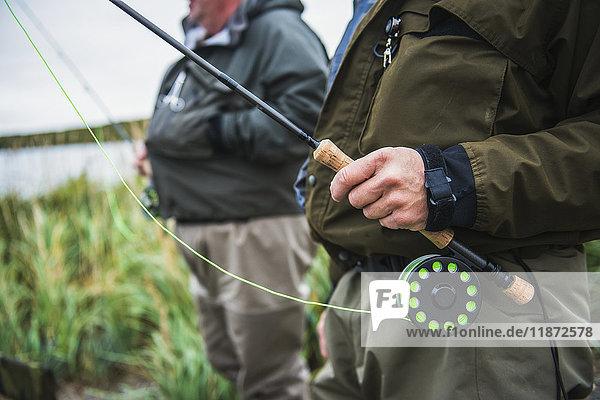 Two fly fishermen standing along the Ugashik River  Southwest Alaska  USA