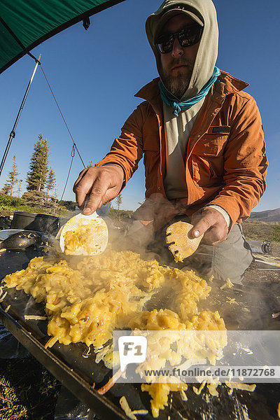 A backcountry guide prepares breakfast for clients during a trip in Lake Clark National Park & Preserve  Southcentral Alaska  USA