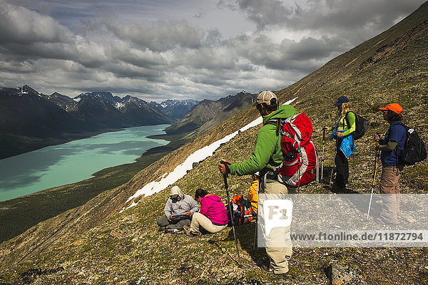 A group of hikers rest on a mountain ridge above the Twin Lakes in Lake Clark National Park & Preserve  Southcentral Alaska  USA
