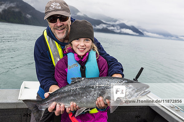 Father and daughter holding up a Silver Salmon while on a boat  Seward  Southcentral Alaska  USA