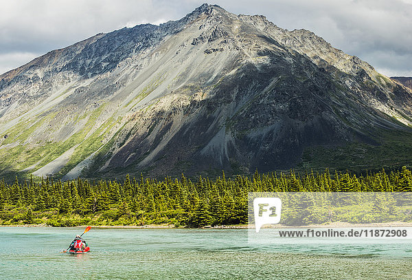A kayaker paddles across one of the Twin Lakes in Lake Clark National Park & Preserve  Southcentral Alaska  USA