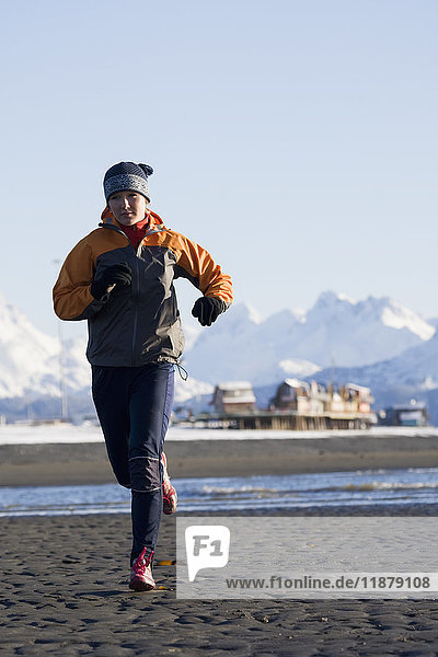 'A young woman jogs on the wet beach; Homer  Alaska  United States of America'