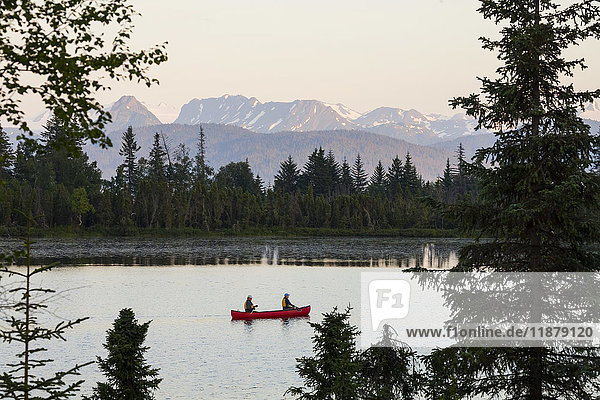 'A couple canoeing on Stone Step Lake; Homer  Alaska  United States of America'
