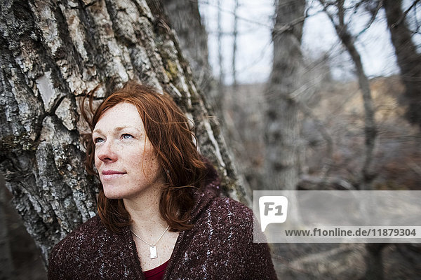 'Portrait of a woman with red hair against a tree and looking contemplative; Homer  Alaska  United States of America'