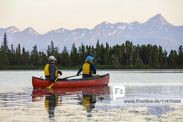 'A couple canoeing on Stone Step Lake; Homer  Alaska  United States of America'