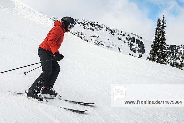 'A downhill skier in a red coat skiing on the snow covered Rocky Mountains; Whistler  British Columbia  Canada'