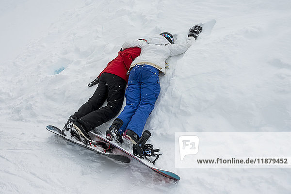 'Two young snowboarders laying together resting in the snow; Whistler  British Columbia  Canada'