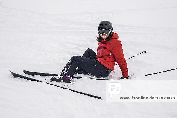 'A skier in a red coat sitting in the snow; Whistler  British Columbia  Canada'