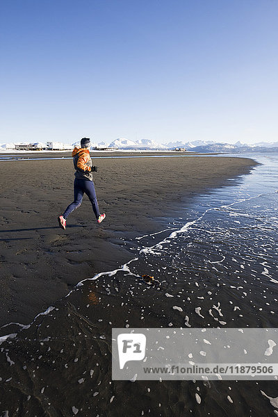 'A young woman jogs on the wet beach at the water's edge; Homer  Alaska  United States of America'