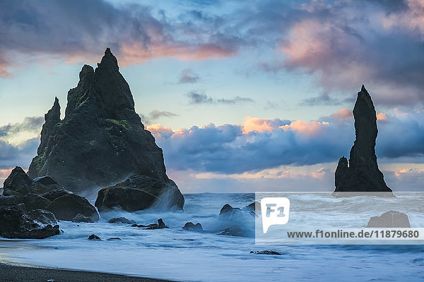 'The sea stacks known as Reynisdrangar with waves and sunrise happening above them  South Coast; Iceland'