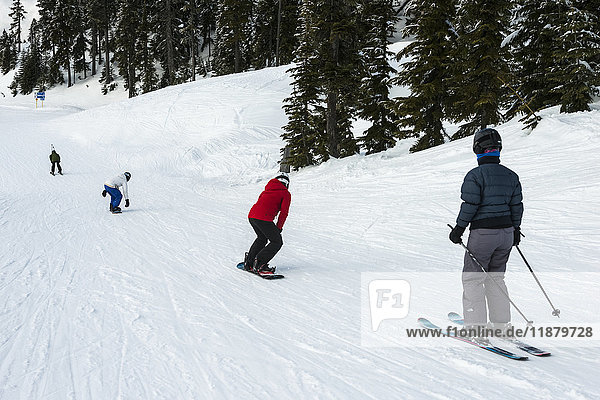 'A group of skiers and snowboarders making their way down a hill; Whistler  British Columbia  Canada'