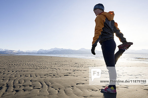 'A young woman stretches on the wet beach before running; Homer  Alaska  United States of America'