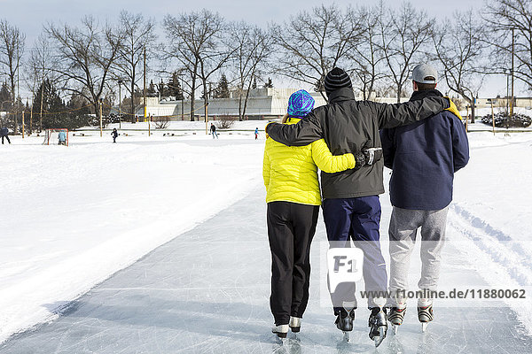 'Two males and one female skating arm in arm on freshly groomed ice on pond with community centre in the background; Calgary  Alberta  Canada'