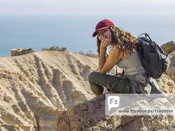 'A young woman sits on a rock looking back and posing for the camera with a view of Ein Gedi Nature Reserve  Dead Sea District; South Region  Israel '
