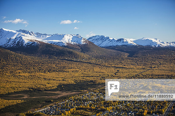 'Eagle River Valley  homes nestled among the trees in the foreground  autumn coloured trees filling the valley  snow covering the Chugach Mountains in the background  South-central Alaska; Eagle River  Alaska  United States of America'