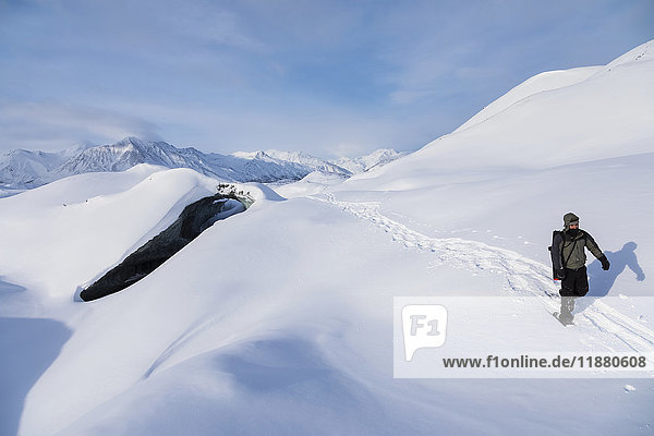 'A snowshoer crosses over the snow-covered Canwell Glacier in winter; Alaska  United States of America'