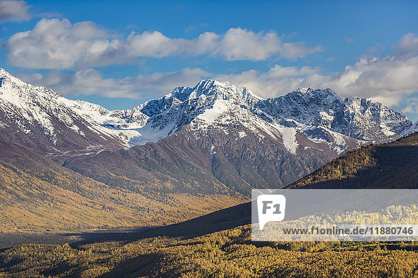 'Eagle River Valley  homes nestled among the trees in the foreground  autumn coloured trees filling the valley  snow covering the Chugach Mountains in the background  Eagle River  South-central Alaska; Alaska  United States of America'