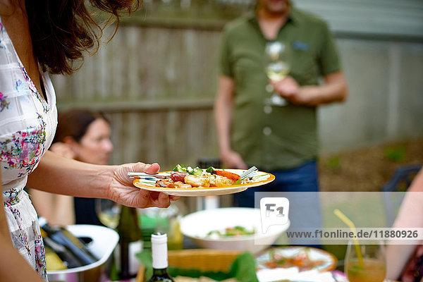 Frau auf Gartenparty  die einen Teller mit Essen hält  Mittelteil