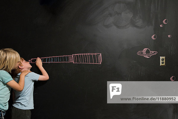 Boys looking through imaginary telescope drawn on blackboard