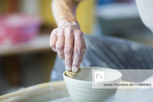 Senior woman in pottery workshop  making bowl  close-up