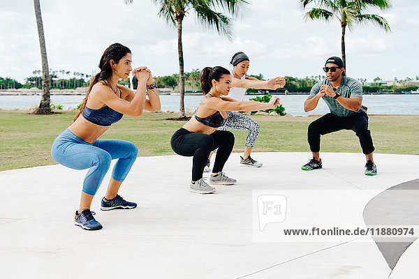 Drei Frauen trainieren mit einem persönlichen Trainer  South Point Park  Miami Beach  Florida  USA