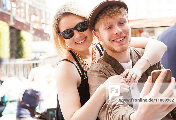 Young couple  outdoors  taking selfie  using smartphone