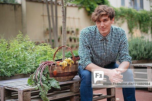 Porträt eines Mannes  der im Garten sitzt und lächelnd in die Kamera schaut