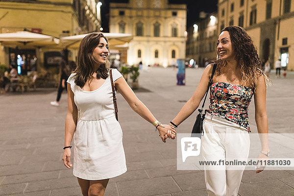 Junge Frauen in der Stadt halten sich an den Händen und lächeln