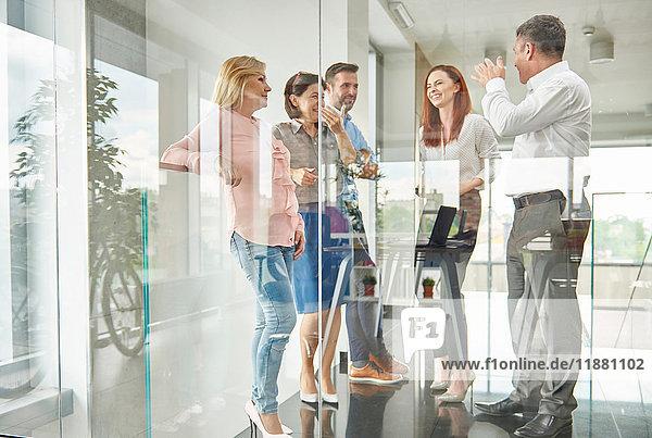 Blick durch das Glas von Kollegen  die im Büro stehen und reden