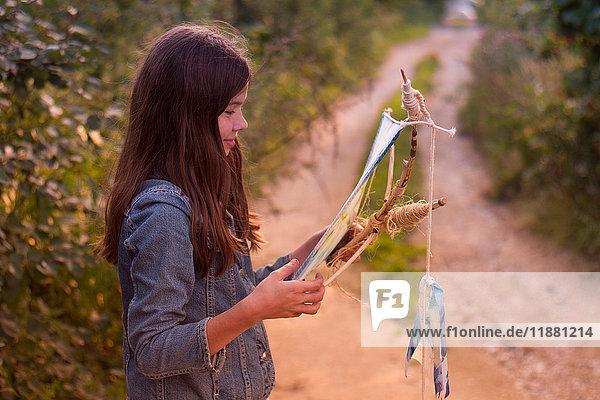 Teenage girl gazing at kite on dirt track