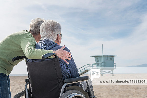 Senior man in wheelchair with wife looking out from beach  Santa Monica  California  USA