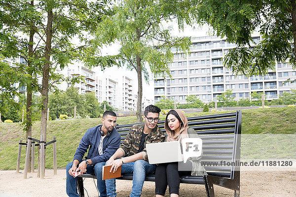 Drei Freunde  die auf einer Parkbank sitzen und auf einen Laptop schauen