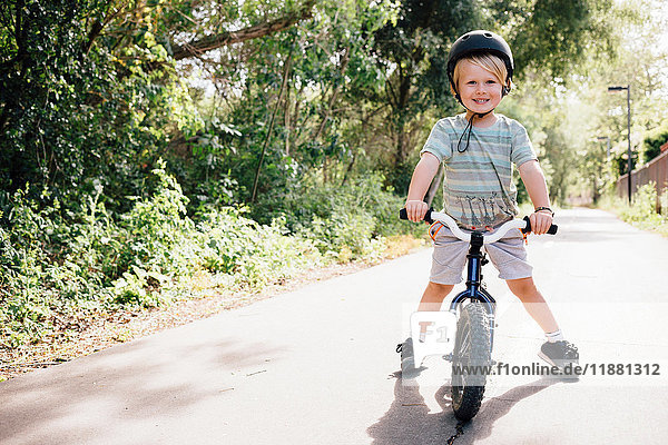 Portrait of young boy riding bicycle outdoors
