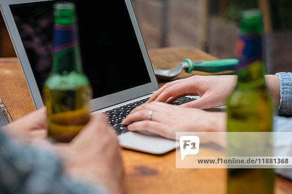 Ausschnitt eines Paares beim Biertrinken am Laptop