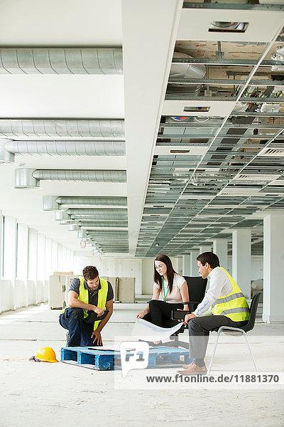 Drei Personen sitzen in neu errichteten Büroräumen und sehen sich Baupläne an