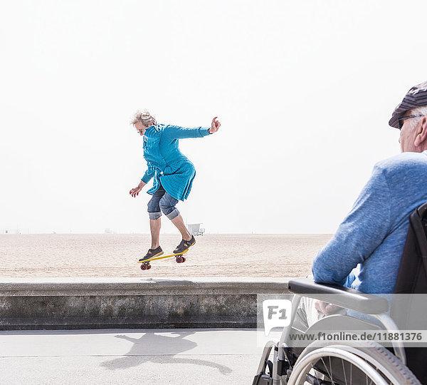 Senior man in wheelchair watching wife doing skateboard trick at beach  Santa Monica  California  USA