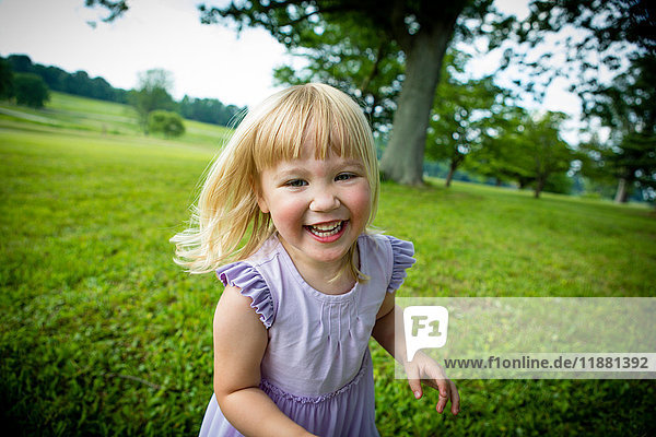 Portrait of blond haired girl running in rural field