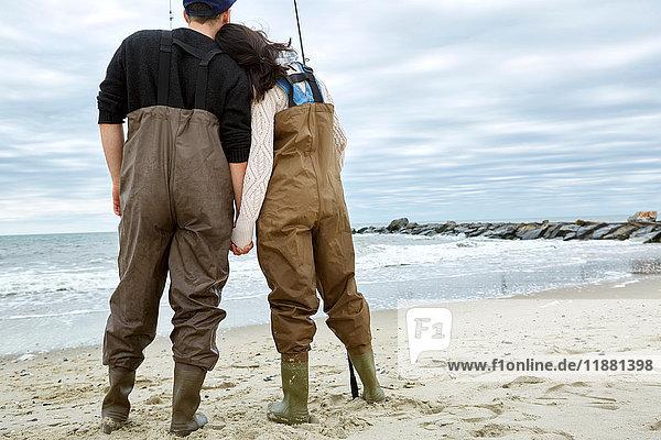 Rückansicht eines romantischen jungen Paares in Wathosen zum Meeresangeln am Strand