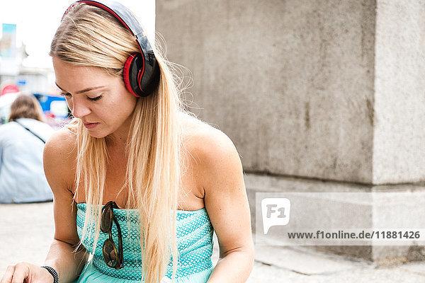 Mittlere erwachsene Frau  im Freien  Kopfhörer tragend  nach unten schauend