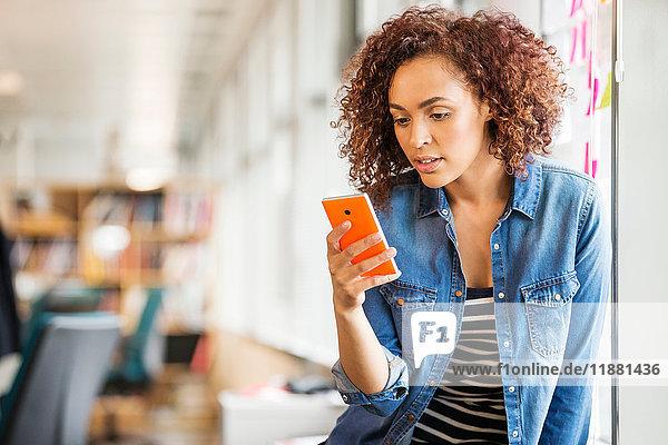 Digitaldesignerin auf Büroschreibtisch mit Blick auf Smartphone