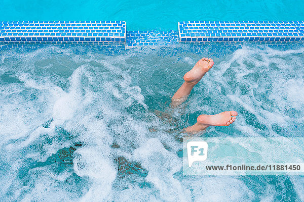 Overhead view of diving boy's feet in splashing outdoor swimming pool