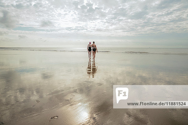 Mother and daughter heading to sea  Folkestone  UK